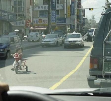 Niño en un triciclo en medio de la calle