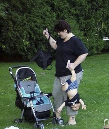 Una mamá con su bebe colgando del brazo
